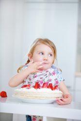 Blondes Kind nascht von einer frischen Erdbeertorte am Geburtstag